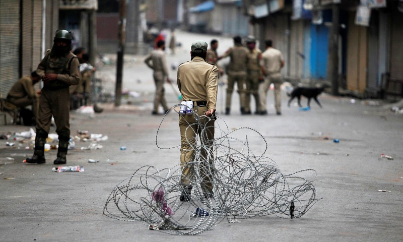 A policeman pulls concertina wire to lay a barricade on a road during a curfew in Srinagar. —Reuters