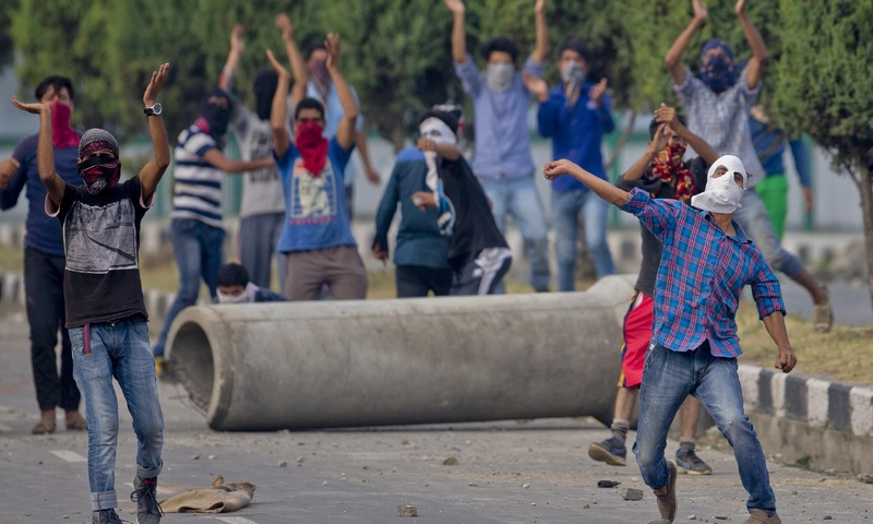 A Kashmiri protester throws stones at Indian troops as others shout pro freedom slogans in Srinagar. —AP