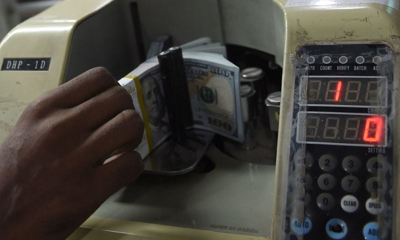 KARACHI: A currency dealer counts US dollars with a machine at a currency exchange.—AFP
