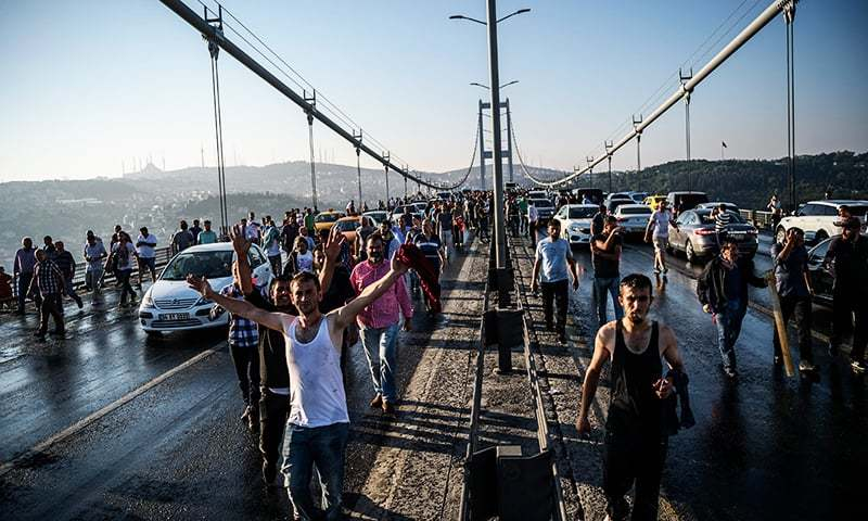 People react after they took over military position on the Bosphorus bridge in Istanbul on July 16, 2016. — AFP