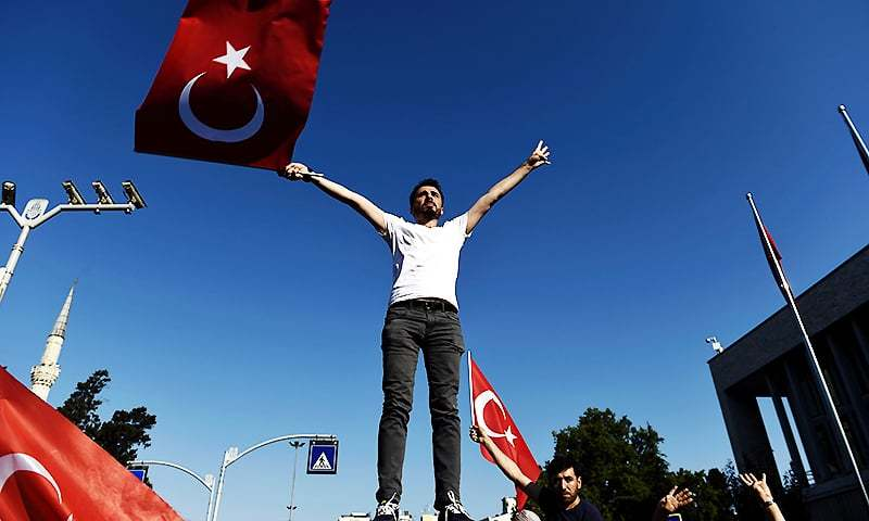 A man waves a Turkish flag during a demonstration in Istanbul in support the government on July 16, 2016, following a failed coup attempt. ─ AFP