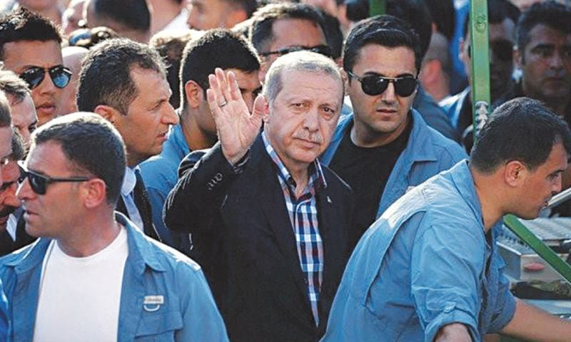 SURROUNDED by his bodyguards, Turkish President Recep Tayyip Erdogan waves to his supporters.