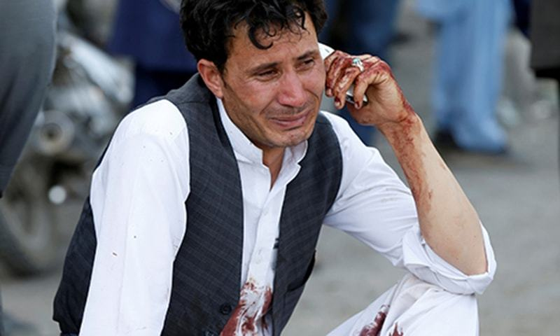 A man talks on his phone after a suicide attack in Kabul. —Reuters