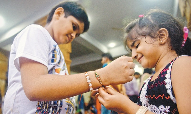A girl ties the sacred rakhi thread around her brother's wrist at the Shri Laxmi Narayan Temple on Thursday.—Fahim Siddiqi / White Star
