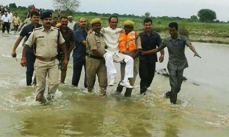 Shivraj Singh Chouhan being helped by police team in flood area.—Photo Courtesy: The Indian Express