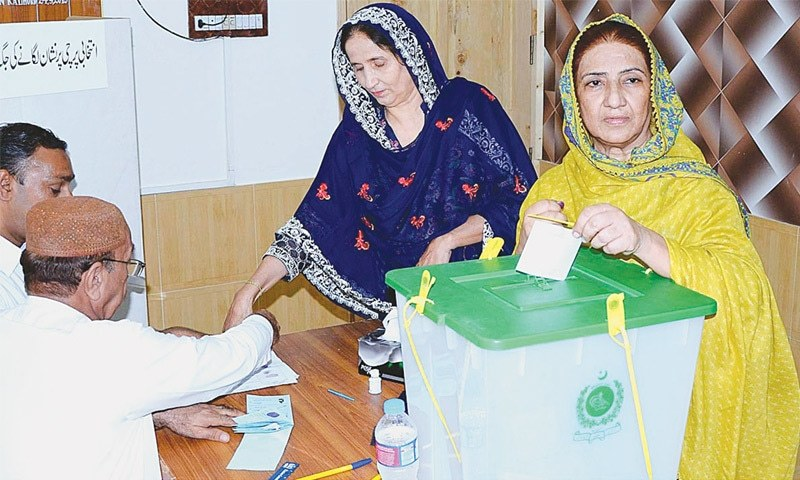 A MEMBER casts her vote during the election for the slots of chairman and vice chairman of the Larkana district council on Wednesday.—APP