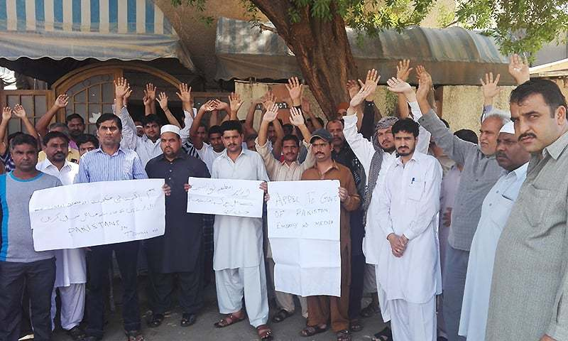 Protesting workers hold signs asking the Pakistani government to intervene. ─ Photo courtesy Basit Sheikh