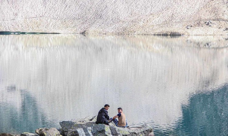 The hard trek is worth the views at the glacial lake.  Trekkers rest at the edge of  Bashigram Lake