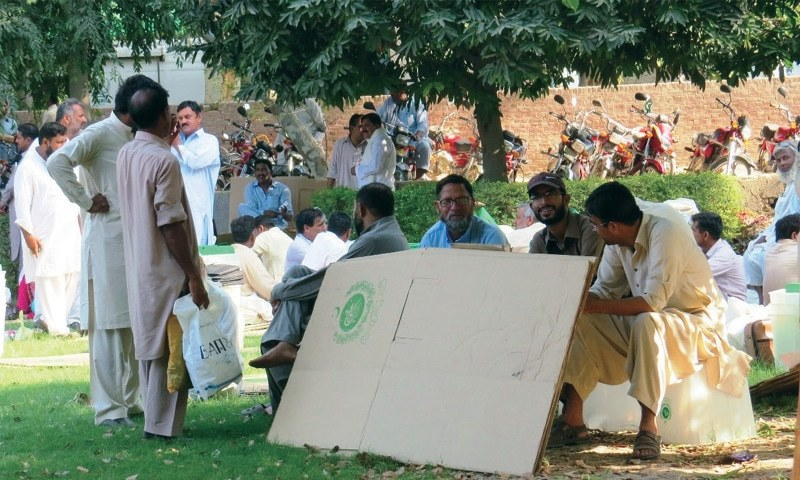 SAHIWAL: Election staff waiting for transport to dispatch material to polling stations in Chichawatni.—Dawn