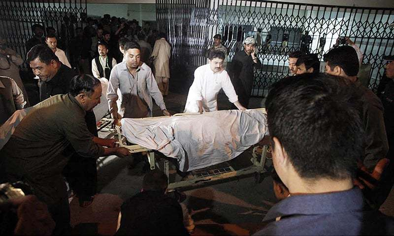 Men seen shifting body of one of the four women who were killed by of unknown assailants. —Online