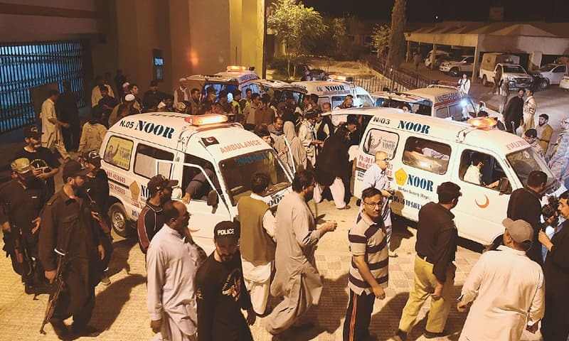 QUETTA: Security officials and residents gather around ambulances carrying from the hospital the bodies of women killed in an attack on a bus on Tuesday.—AFP