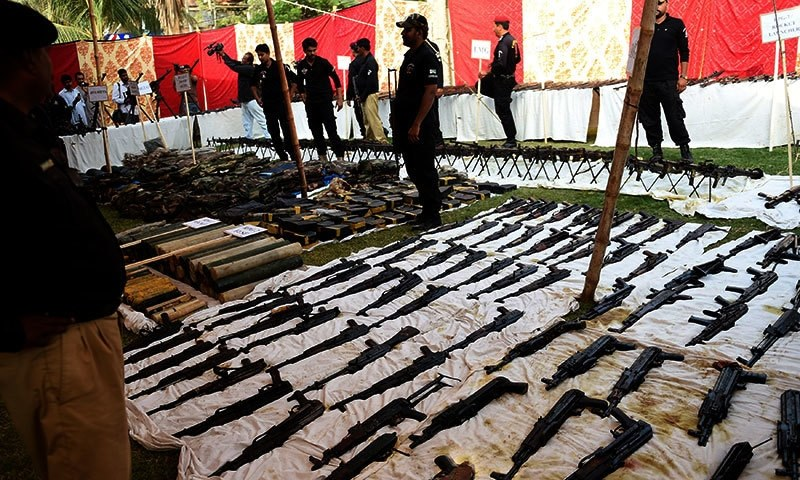 Policemen stand beside seized weapons displayed for the media in Karachi. —AFP