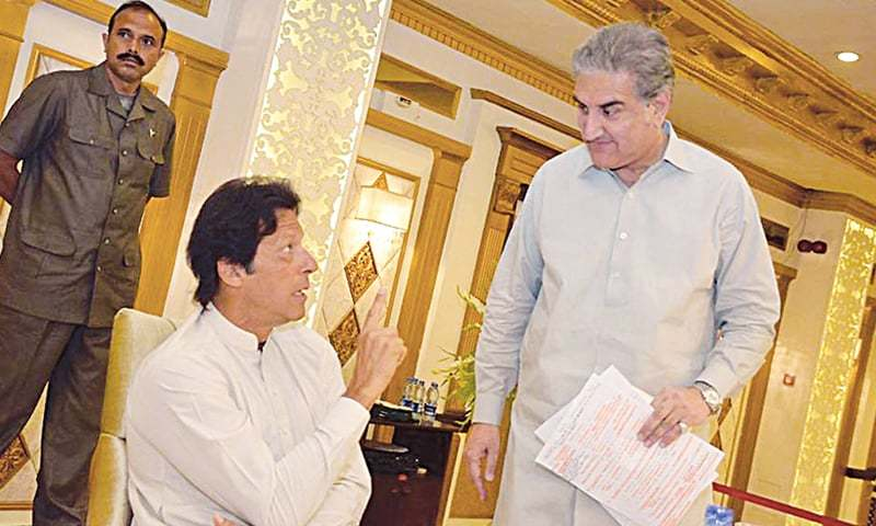 PTI chief Imran Khan talking to Shah Mehmood Qureshi at a meeting of his party on Thursday.—INP