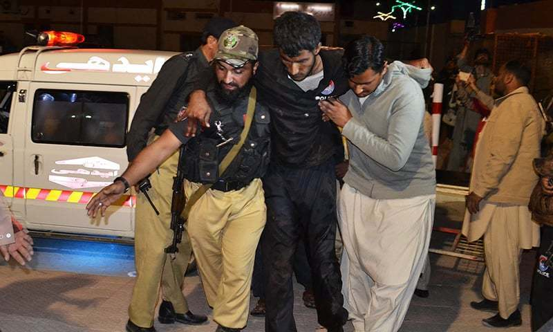 A volunteer and a police officer rush an injured person to a hospital in Quetta. —AP