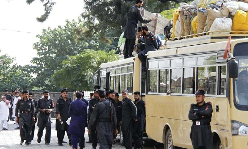 FC personnel disembark from a bus at the community centre in Aabpara on Wednesday. — Photo by Tanveer Shahzad