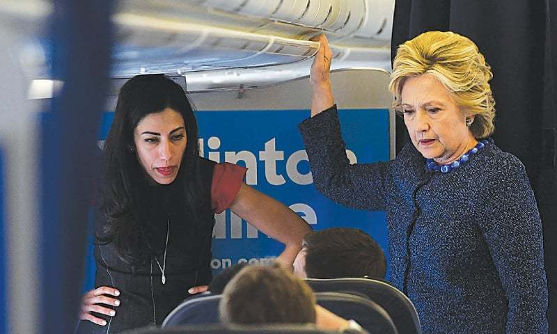 Hillary Clinton talks to staff as aide Huma Abedin (L) listens onboard their campaign plane at the Westchester County Airport in White Plains, New York, on Friday.— AFP