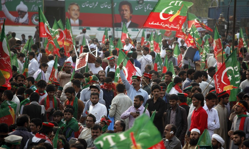 PTI supporters wave party flags while taking part in a rally in Islamabad. —AP