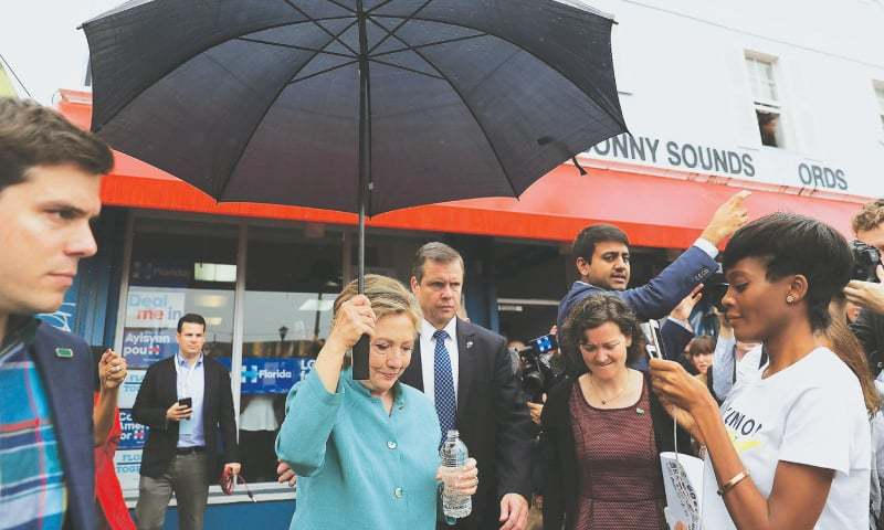 Democratic presidential candidate Hillary Clinton holds an umbrella while leaving a campaign field office in Miami, Florida, on Saturday.—AFP (Right) Republican presidential candidate Donald Trump attends a campaign event in Hershey, Pennsylvania, on Friday.—Reuters