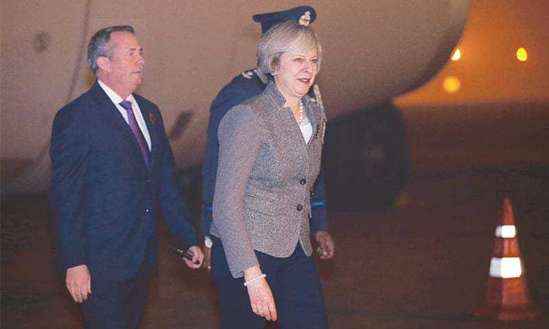 New Delhi: Britain's Prime Minister Theresa May walks towards her car after her arrival at the airport on Sunday.—Reuters
