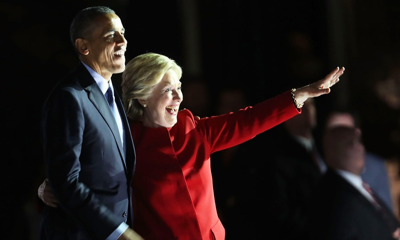 Hillary Clinton stands with Barack Obama at an election eve rally. — AFP