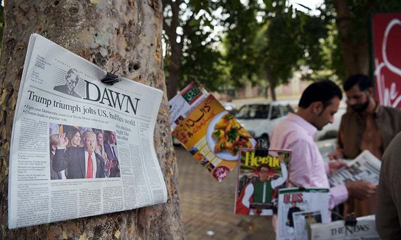 Pakistani residents read newspapers with coverage of Donald Trump's victory in the US presidential election in Islamabad. ─ AFP