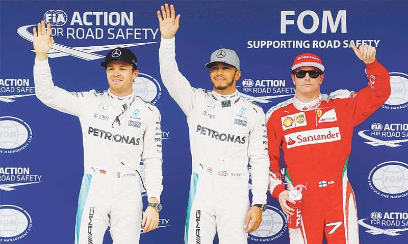 SAO PAULO Mercedes' Lewis Hamilton of Britain celebrates pole position for the Brazilian Grand Prix next to his team-mate Nico Rosberg of Germany and Ferrari's Finnish driver at the Circuit of Interlagos.—Reuters