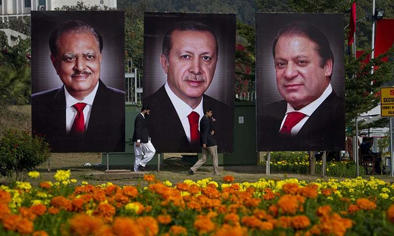 People walk pasts billboards showing the portraits of Turkish President Recep Tayyip Erdogan, President Mamnoon Hussain and Prime Minister Nawaz Sharif to welcome Erdogan. ─AP