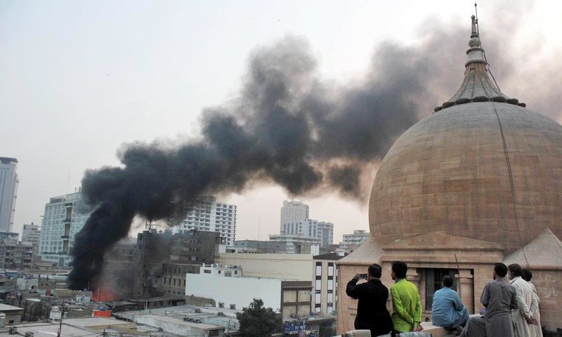 Men look at smoke rising high from chemical store which caught fire near Swaminarayan Mandir. —Online