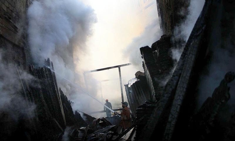 Fire fighter extinguishing fire which erupted in Haji Camp Timber Market. —Online