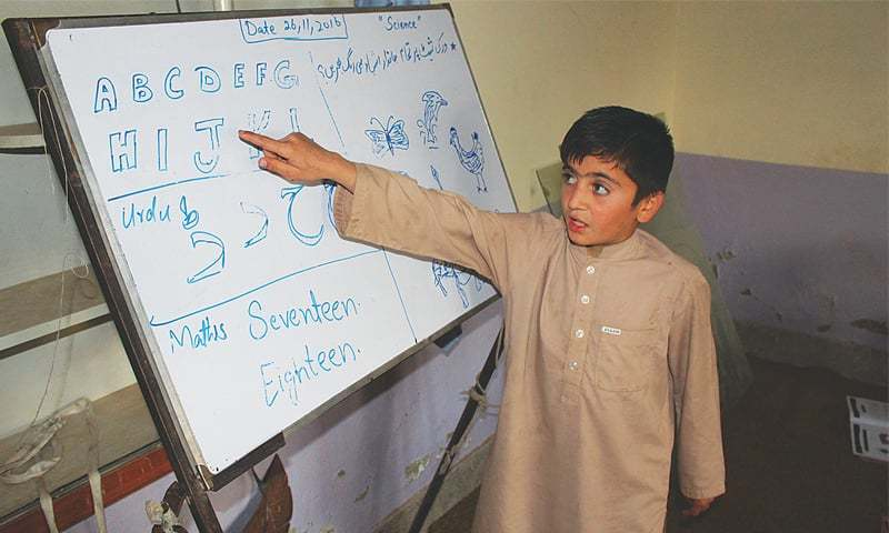 Khalid Khan standing before the whiteboard to read out a lesson at an Alternative Learning School at Bara in Khyber Agency.—Dawn