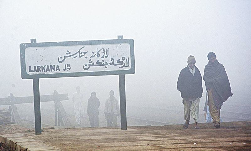 "LARKANA: People walk past the Larkana railway junction on Monday. For the last two days, a dense fog has enveloped cities and towns in upper Sindh, including Larkana, Jacobabad, Sukkur and Moenjodaro, from midnight to noon, says meteorological department official Azizullah Tunio. According to Mr Tunio, who is based in Larkana, the phenomenon will go on for the next few days. ""The fog is so dense that at times it is very difficult to see beyond 10 to 15 feet,"" he said, adding that on Monday, from 5am to 11am, the visibility level dropped and remained around four metres.—APP"