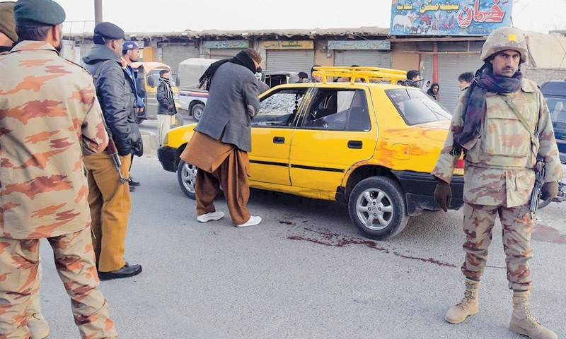 SECURITY personnel gather around a cab after it came under fire on Friday.—INP
