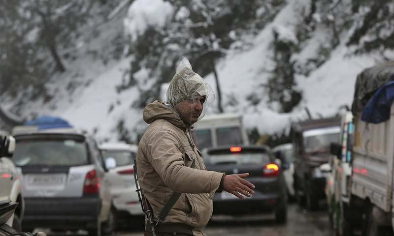 A police man tries to direct traffic after vehicles got stranded due to heavy snow fall on the Jammu-Srinagar highway at Patnitop in Udhampur district of Jammu and Kashmir state. ─AP