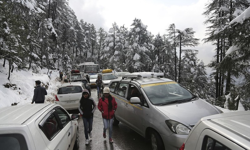 Passengers walk past vehicles stranded due to heavy snow fall on the Jammu-Srinagar highway at Patnitop. ─AP