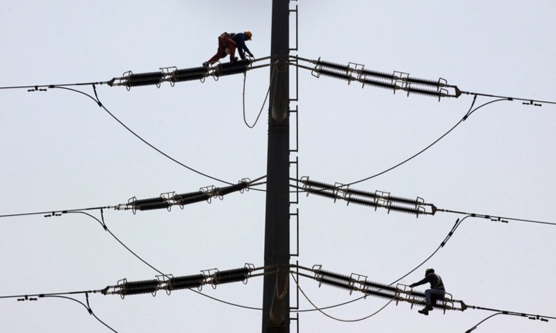 KARACHI: Employees of K-Electric fix cables on a power transmission tower.—Reuters/File