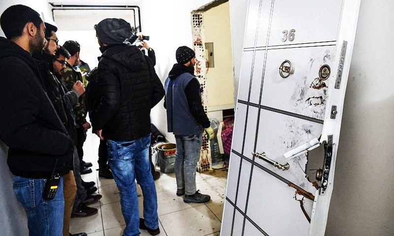 Turkish plain clothes police officers wait next to a damaged door at the apertment where the main suspect in the Reina nightclub rampage was arrested by Turkish police the night before, in Istanbul on January 17.—AFP
