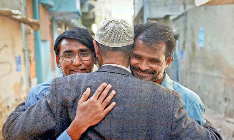 Bhatti (left) and Sulaiman finally have something to smile about as they embrace their cousin outside his home in Karachi.— Fahim Siddiqi/ White Star