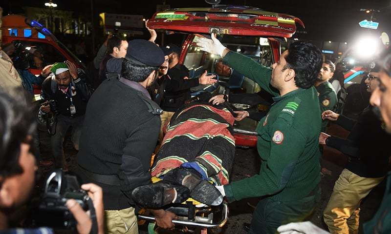 Policemen move an injured victim from a blast site into a vehicle after a powerful explosion in Lahore on February 13.— AFP