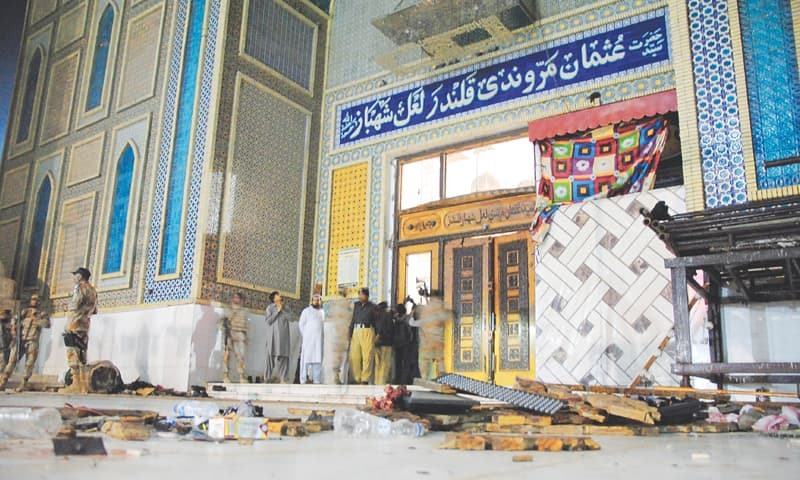 THE floor of the shrine is strewn with debris as security personnel gather at the place after the blast on Thursday. —Photo by Yousuf Nagori