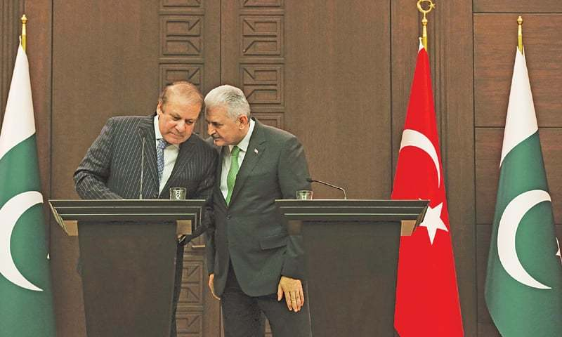 PRIME Minister Nawaz Sharif and his Turkish counterpart Binali Yildirim talking to each other ahead of a joint press conference on Thursday.—AP