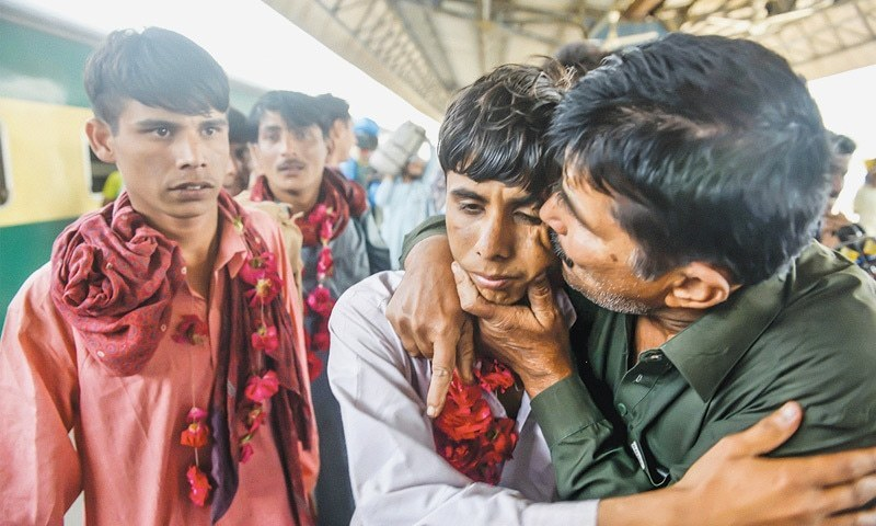 FATHER is reunited with his three fishermen sons upon their arrival at the Cantonment Railway Station on Friday.—Fahim Siddiqi/White Star
