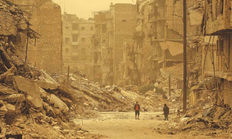 Aleppo: Syrians walk amidst debris during a sandstorm in a once rebel-held Kastal al Harami neighbourhood on Friday.—AFP