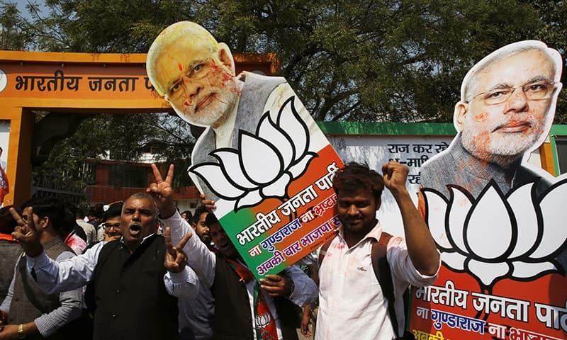 Bharatiya Janata Party supporters raise cutouts of Indian Prime Minister Narendra Modi as they celebrate winning seats in the state of Uttar Pradesh in Lucknow, India, Saturday.— AP