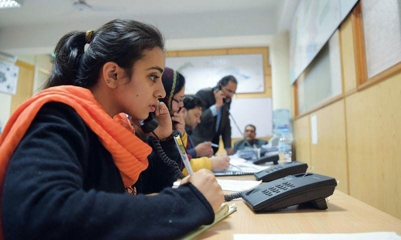 Staff at Pakistan Bureau of Statistics give information on public helplines on Monday about the census.— AFP