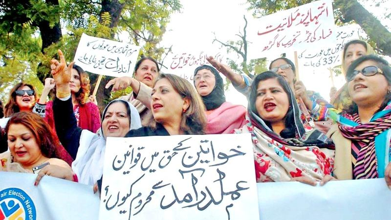 Women rights activists hold placards during a rally held in connection with International Women's Day on Tuesday. — Online