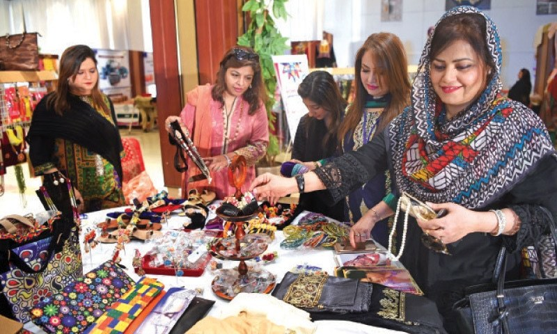 Visitors take interest in hand-made items displayed at the trade fair in Peshawar on Tuesday. — White Star