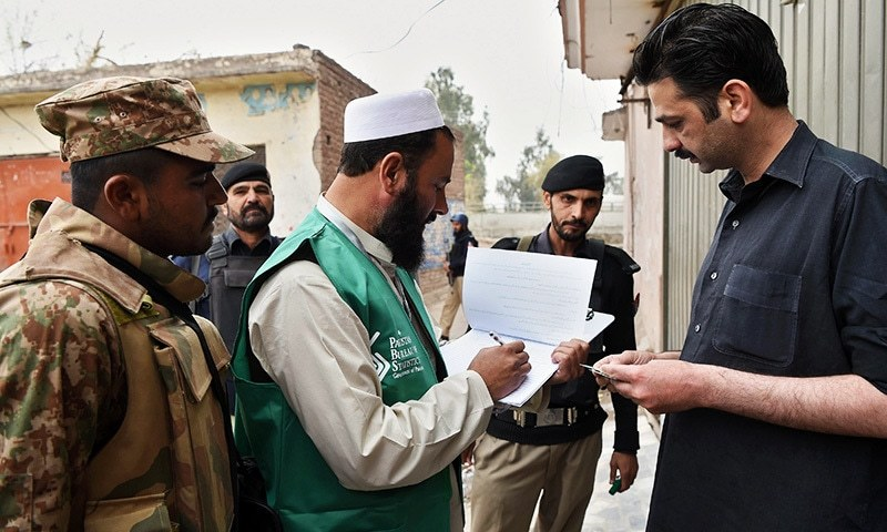 An official from the Pakistan Bureau of Statistics collects information from a resident during a census as security personnel guard them in Peshawar on March 15.— AFP