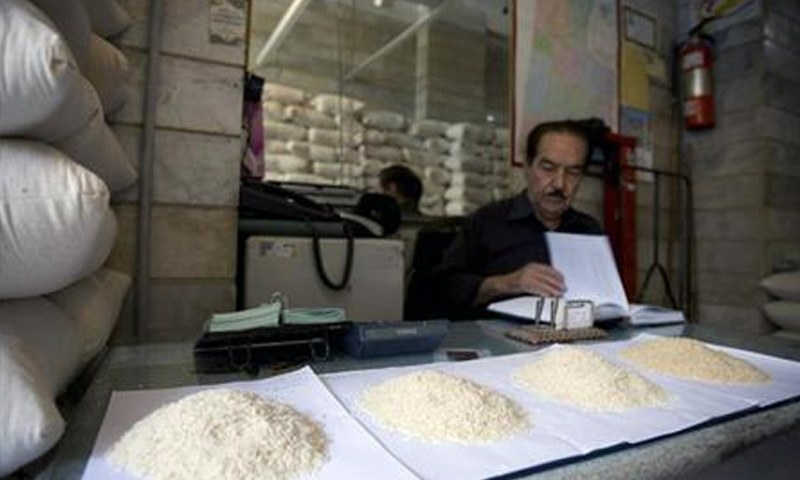 TEHRAN: Samples of rice are seen on the desk as a wholesaler checks his books in this file photo.—Reuters