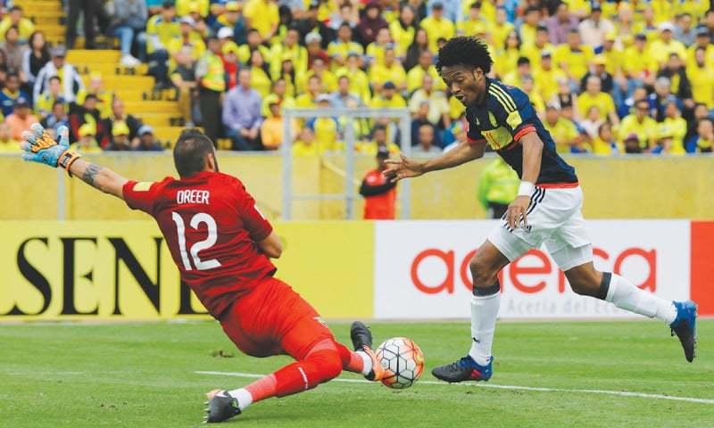 QUITO: Colombia's Juan Cuadrado dribbles past Ecuador goalkeeper Esteban Dreer to score during the 2018 World Cup qualifier at the Atahualpa Olympic Stadium.—AP