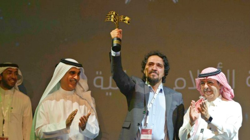 Saudi actor Mohammed Al-Qess waves his award for best actor in the film The Departings during the closing ceremony of the 4th Saudi Film Festival in Dammam